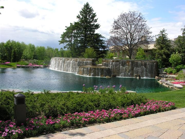 Large Waterfall Flowing Into Man Made Pond In Front Yard