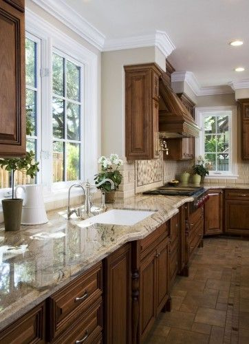 Dark cabinets, light counter tops, medium floor with champaign walls and white windows..<3