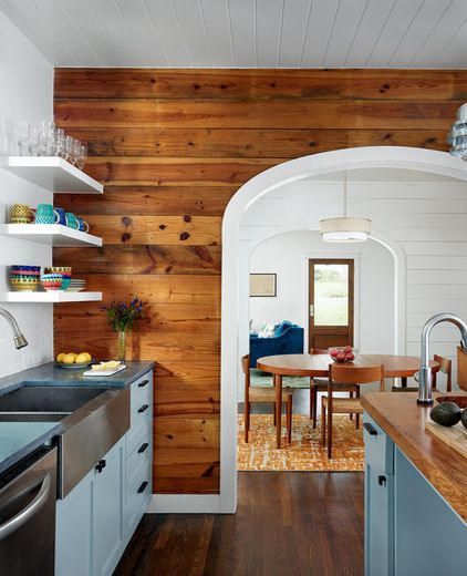 Wood paneled wall (& white molding/arch stainless farm sink) gives this kitchen a totally different vibe