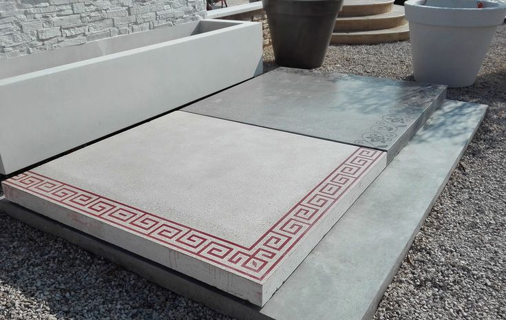 Dalle carrée de grand format (1 m 50) préfabriquée en béton armé. Finition béton lisse (poncé / poli), ton pierre. Pose sur plots ou pieux.