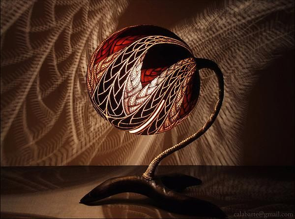 Calabarte is an artist from Poland. He sculpts elaborated patterns on gourds which come from Senegal. When the lamp is switch on, the light amazes us with the fairy atmosphere created.