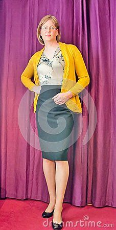 A smart and casually dressed Woman wearing a yellow cardigan, orange top and print skirt stood by a curtain.