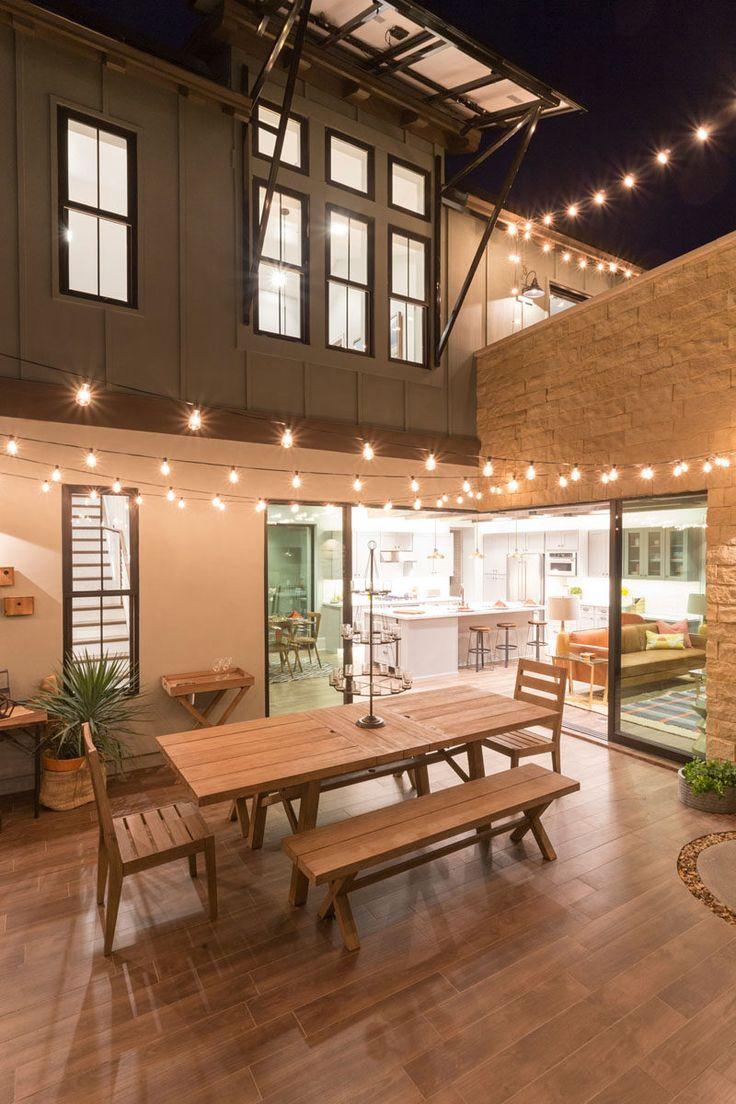 Pátio com mesa para refeições e varal de lâmpadas