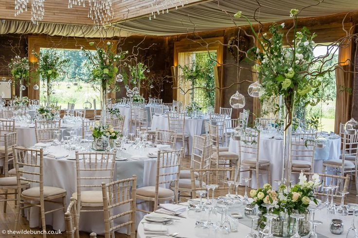 Top UK Wedding florists, The Wilde Bunch going 'Wilde' with an innovative and stunning design at top Gloucester venue, Elmore Court. Once the light falls and those hanging tea lights illuminate the tall vase designs the whole venue shimmers. See this image in full size to fully appreciate it along with our other Elmore Court designs at http://www.thewildebunch.co.uk/#/elmore-court/4593918319