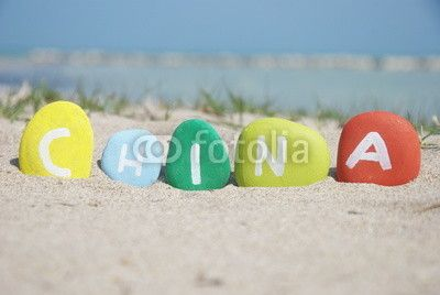 China on colourful stones on the sand