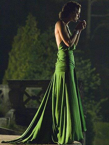 "Keira Knightley's green evening gown in ""Atonement"". Designed by Jacqueline Durran.    It's made of yards and yards of bias-cut (diagonally cut, in order to skim the body's curves) green silk.    You can't see from this picture, but the from afar the bodice seems to have beads or dark sequins sewn to it. In fact, it has been laser-cut in a very intricate pattern. The skirt is also split almost all the way up the front, a split partly hidden by the knotted sash and only revealed when she…"