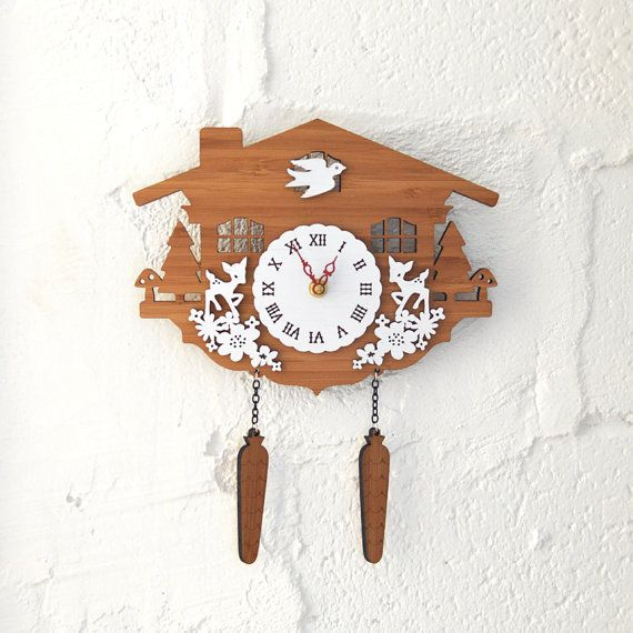 Everything you love about the look of traditional cuckoo clock - the whimsy and the charm are fully intact in this modern take on the timeless design.  ITEM SPEC:  • Overall size is 10 x 12 • Made with eco-friendly 3ply bamboo layered with 1 ply bamboo painted in white • Choose the color of hour & minute hands • No second hand • Using silent motor • Ships well protected • Clock requires one AA battery to operate (not included) • No actual cuckoo mechanism  Ships within 2-6 business days…