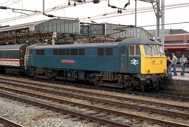 """86211 (E3147) """"CITY OF MILTON KEYNES"""" in its final year of service, waits at Crewe on the 23rd Aug 1986. E3147 first entered service during 1966 after construction by English Electric at Newton-le-Willows. Named """"CITY OF MILTON KEYNES"""" on the 14th May 1982. On the 19th Sept 1986, whilst hauling the 17:20 Liverpool-Euston service, 86211 collided with 86429 """"THE TIMES"""" . Both locos were removed by road to Crewe Locomotive Works and condemned in November. 86211 was cut-up at Crewe during Sept…"""