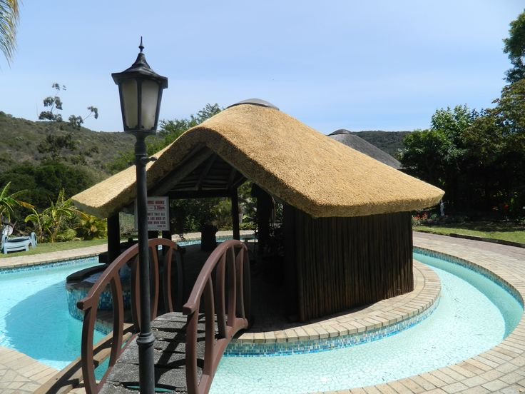 Small thatched lapa on island inside splash pool, with latha walls