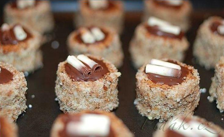 POTŘEBNÉ PŘÍSADY: Na těsto: 14dkg másla 14dkg moučk.cukru 1 vanilkový cukr 14dkg strouhané čokolády 14dkg strouhaných ořechů,6vajec  Na krém: odřezky z placky 10dkg másla 1syrový žloutek 6dkg moučkového cukru trochu rumu-nemusí být  Na ozdobu: perličky čokoládová poleva strouhané ořechy   POSTUP PŘÍPRAVY:  Máslo utřeme s cukrem a van.