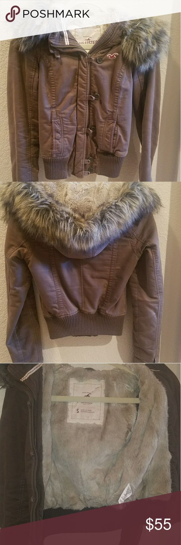 Hollister Jacket with Furry Hood Size small. Very good condition and well taken care of warm brown jacket lined on inner body with cream colored fur. Hood has removable fur, the fur attaches with buttons and snaps. The zipper has caused some discoloration in the zipper flap as shoen in picture 4. Features 2 hand pockets near waist and double zippers. Hollister Jackets & Coats Utility Jackets