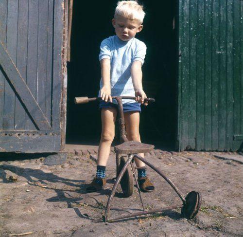 Jongetje met roestige kapotte driewieler voor open schuurdeuren. Nederland, ca.   1963.