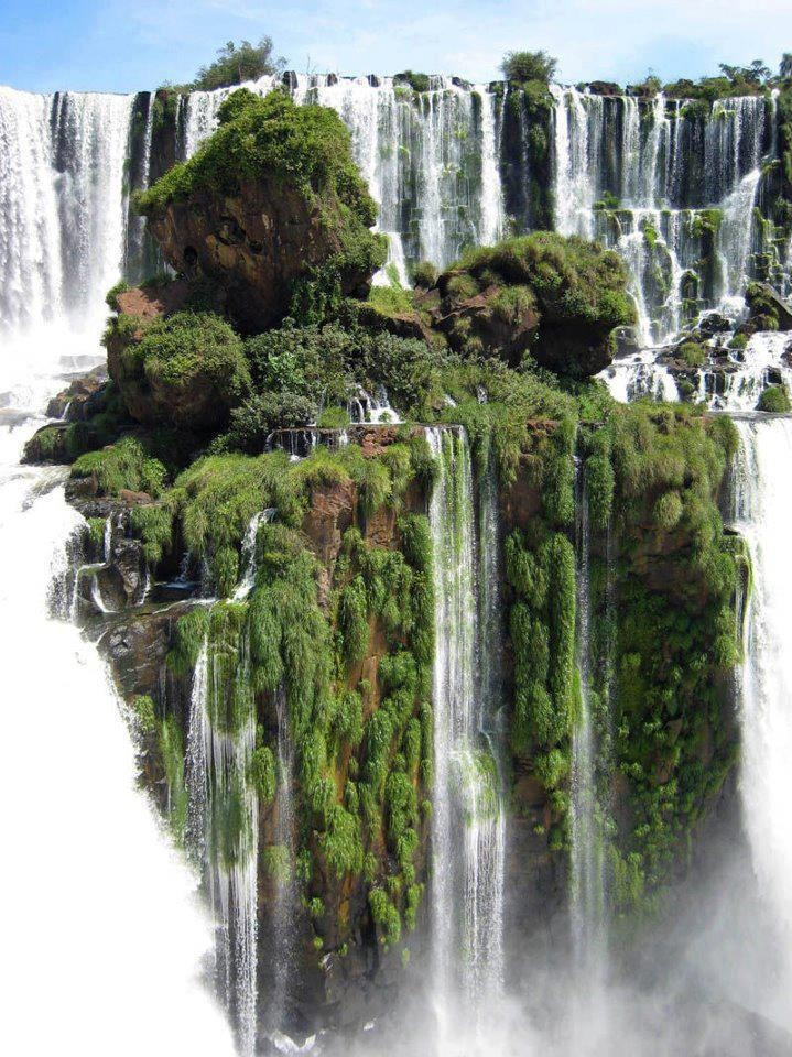 The Waterfall Island at Iguazu Falls.    Iguazu Falls, Iguassu Falls or Iguaçu Falls are waterfalls of the Iguazu River on the border of Brazilian State Paraná and Argentine Province Misiones