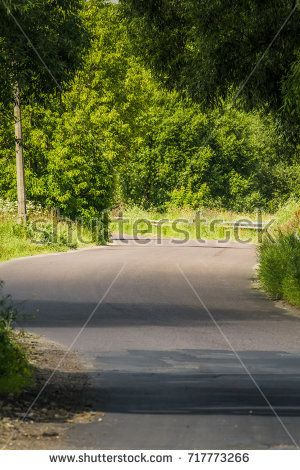 Old cracked, damaged asphalt road in countryside at sunny day.