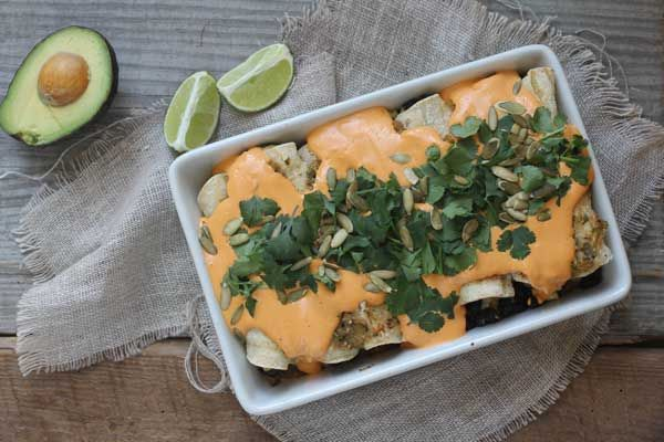 These vegan enchiladas are a favorite in our home! Smoky black beans and veggies, drenched in tomatillo salsa, and smothered in roasted red pepper cashew cream.