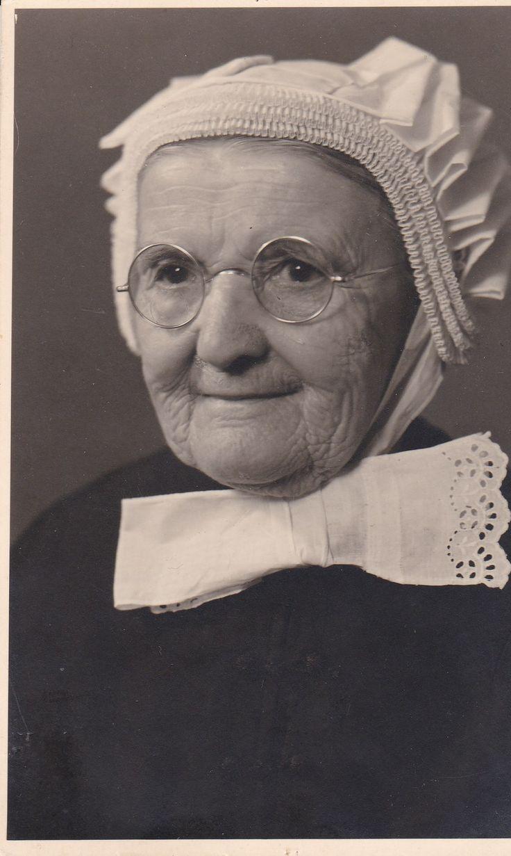 Eindhovens mutsje. Mevr. Smulders-Hoens. Geboren in Nederweert 16-02-1864. Komt in 1891 naar woensel en woonde in de Lijmbeekstraat met haar man. Ze heeft de rest van haar leven altijd in Woensel gewoond. Overleden in Woensel 23-05-1945. Dus is dit een Eindhovens mutsje uit Woensel, met geen spitse voorstroken.. 3 Voorstroken, wat een minimum is. Gewone mensen dus. Muts voor uit de rouw. . Foto gemaakt bij v.d. Kerkhof. Woensel.