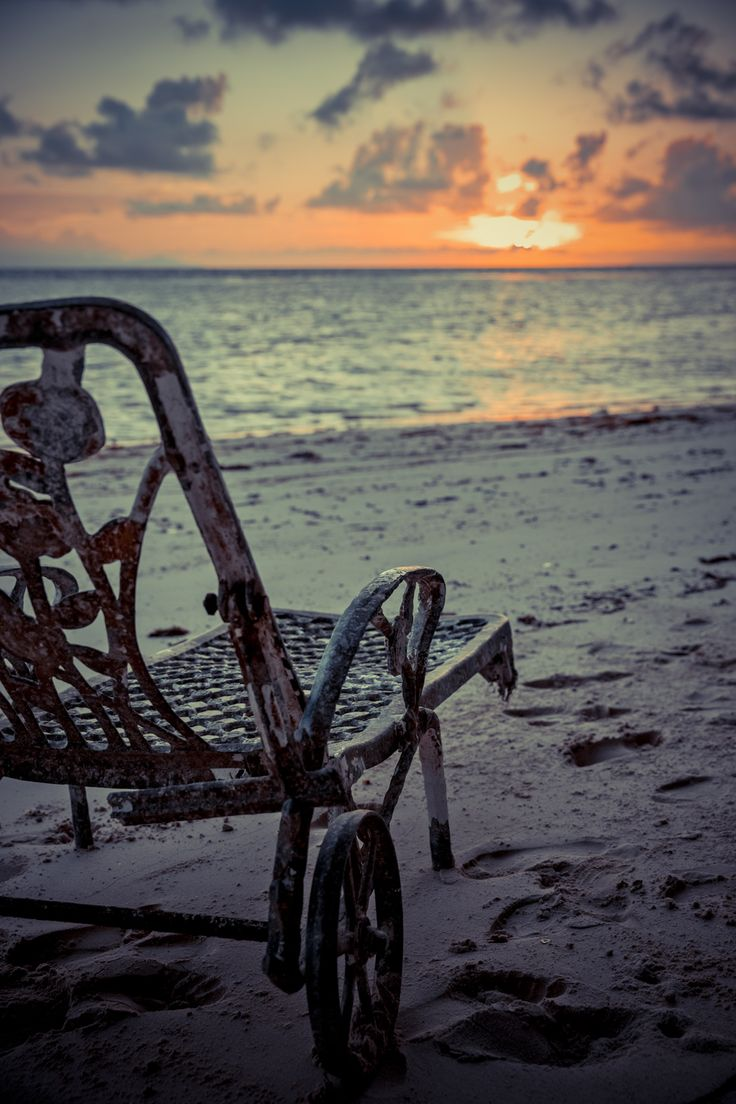 antique deck chairs on the shore of the Indian Ocean, Seychelles Island, sunset