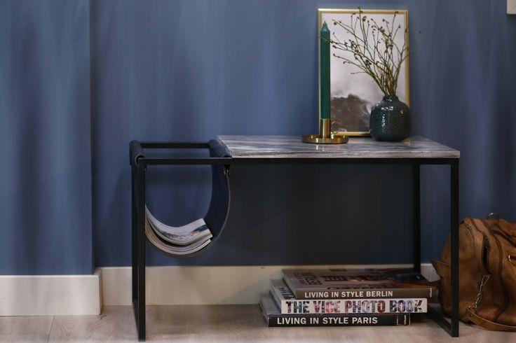 Marmorbord med grå plate og svart lærlomme til magasiner etc.