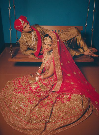 Indian Wedding Photography - Bride in a Bright Red Lehenga with Golden Embroidery with Red Net Dupatta and Groom in a Gold Sherwani   WedMeGood #wedmegood #indianwedding #indianbride ##coupleshot #lehenga #bridal