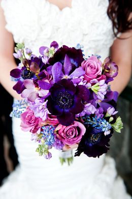 This bouquet, in my opinion, is stunning. I think the center flower is a purple anemone or a peony.