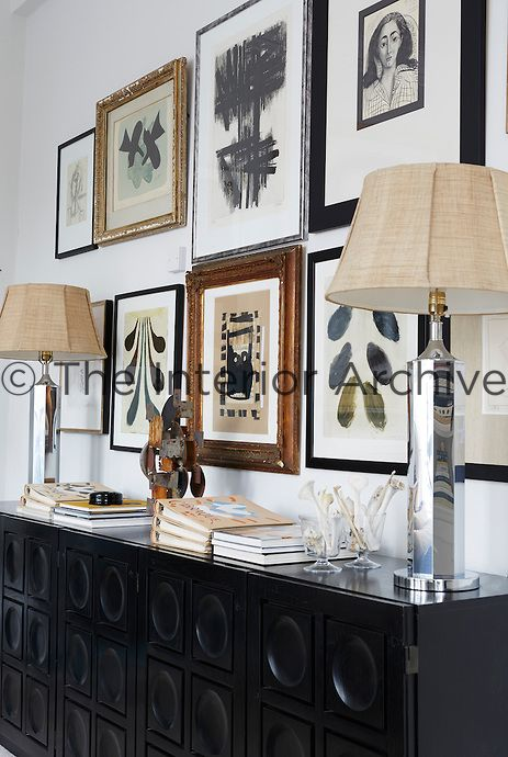Two silver table lamps stand on a sideboard with other items. A collection of artworks are displayed on the wall above.