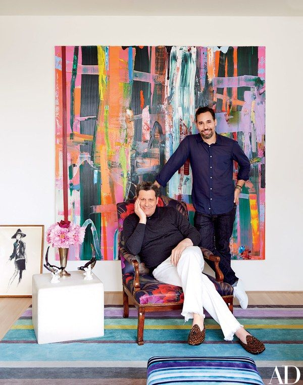 Mizrahi (seated on an antique French armchair upholstered in a linen from his collection for S. Harris) with his husband, Arnold Germer, in the den; the painting is by Tomory Dodge.