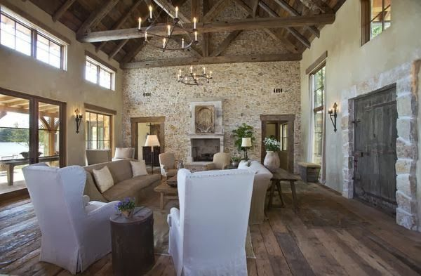 "A Rustic ""Upscale French Barn"" Home on Possum Kingdom Lake in Texas.    Living Room - Magnificent ""French Barn"" living room boasts historic reclaimed materials from Europe. Crates of 17th century rubble were used for the walls. The floors are from a French stable.  The 18th-century limestone mantel in the living room once graced a French farmhouse. The massive front door is easily 300 years old, and it, too, came from a French country house."