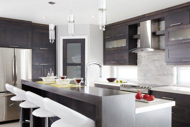 L'îlot et les armoires de la cuisine de style shaker ont été réalisés en placage de merisier teint. Le tout est harmonisé avec un comptoir et tablette «repas» en stratifié.