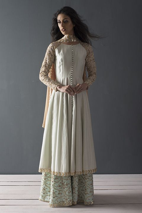 Ivory and turqouise dress has jaal embroidery on the sleeves. The fabric is made of chanderi and silk. pants