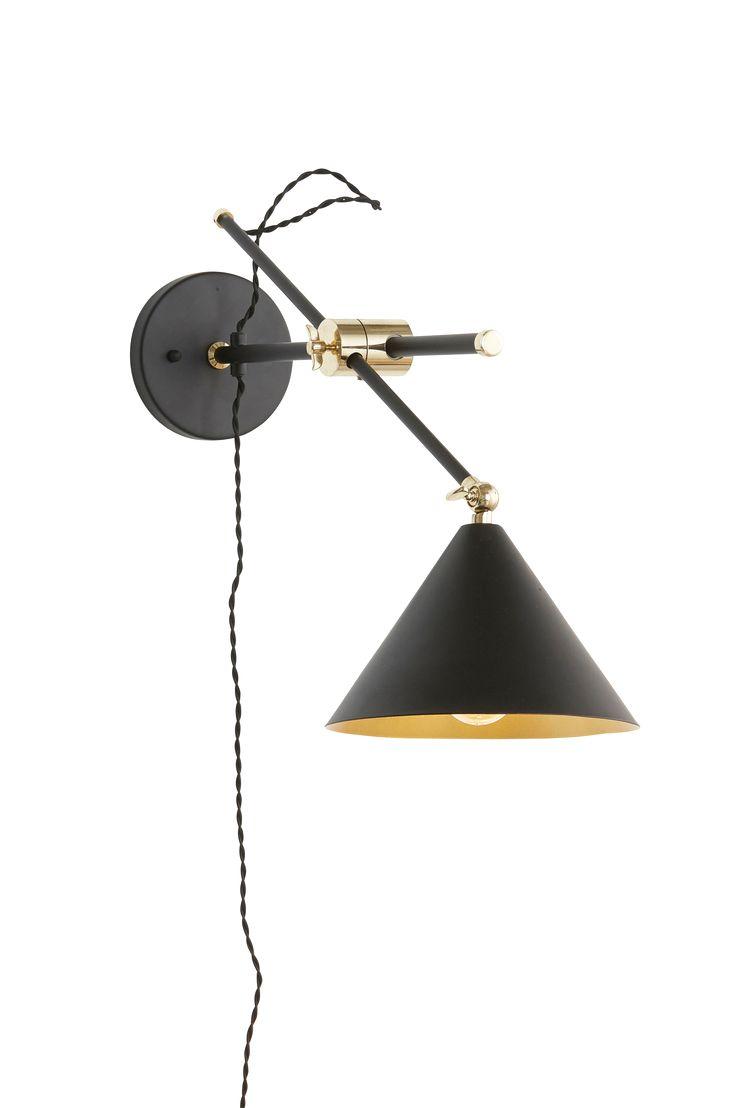 Modern och kaxig vägglampa med toner i svart och matt guld. Tvinnad textilkabel som ger lyxig känsla. Material: Metall. Storlek: 75x22x60 cm. Beskrivning: Vägglampa i metall med ställbar arm och skärm. Svart tvinnad textilsladd, längd 25/150 cm. Glödlampa medföljer ej. Sockel/lampa: 1 st E14, max 40 w glödlampa eller max 7 w lågenergilampa. Tips/råd: Ta upp det matta guldet i fler inredningsdetaljer i rummet, för att få en genomgående stil i inredningen.