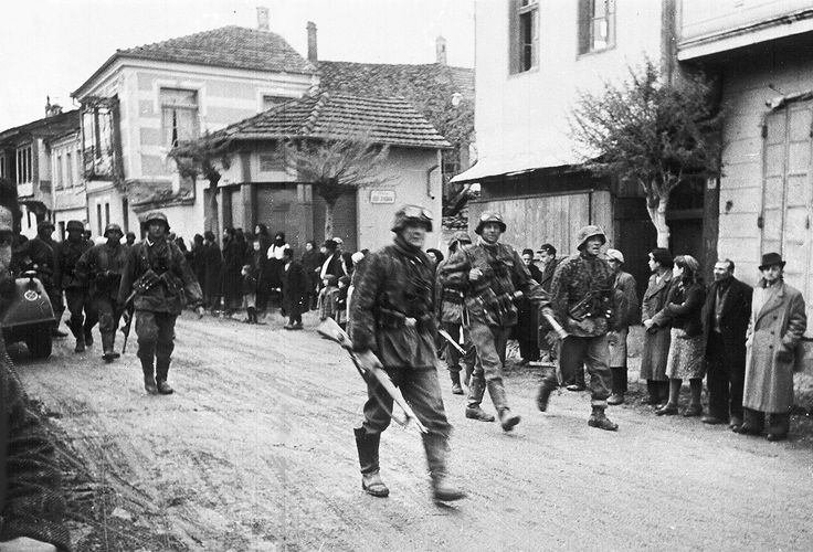 A squad of German soldiers pass through a Greek village, during the occupation of Greece, in May 1941.