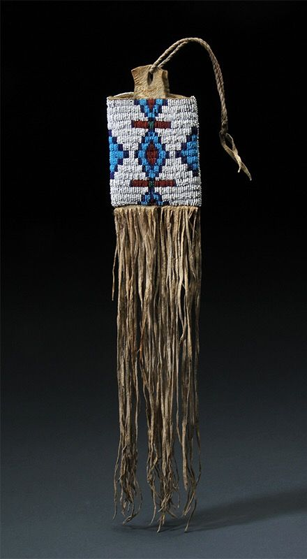 "Cheyenne Mirror Bag, beaded on front and back. Mounted on buffalo hide. C. 1870. 17"" long,  3 1/2"" wide including fringe. Sherwoods Spirit of America."