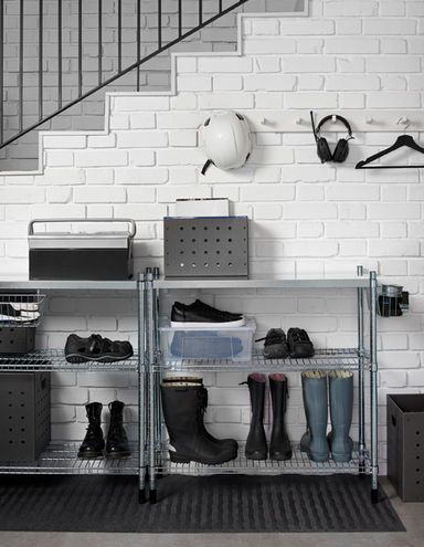 Metal shelving is placed above a doormat to store shoes and several pairs of boots. Storage boxes sit on the top shelf.