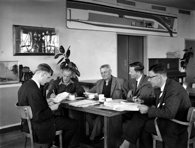 """Afbeelding van de """"wenkenbuscommissie"""" (de commissie die ingebrachte ideeën van werknemers beoordeelt) van de N.V. Nederlandse Staalfabrieken DEMKA (Havenweg 7) te Utrecht, tijdens een overleg, met van links naar rechts drs. H. den Hertog, A. Verstraeten, dipl. ing. W.J.A. Krause, ir. H. Hupkes en mr. J.F.L. Blankenberg. 1962"""