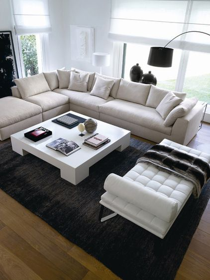 Good living room setup - TV would be behind the white settee. Easy for people to sit there when a large group is chatting, and since it's backless, it doesn't obstruct the view of the fireplace and TV when desired.