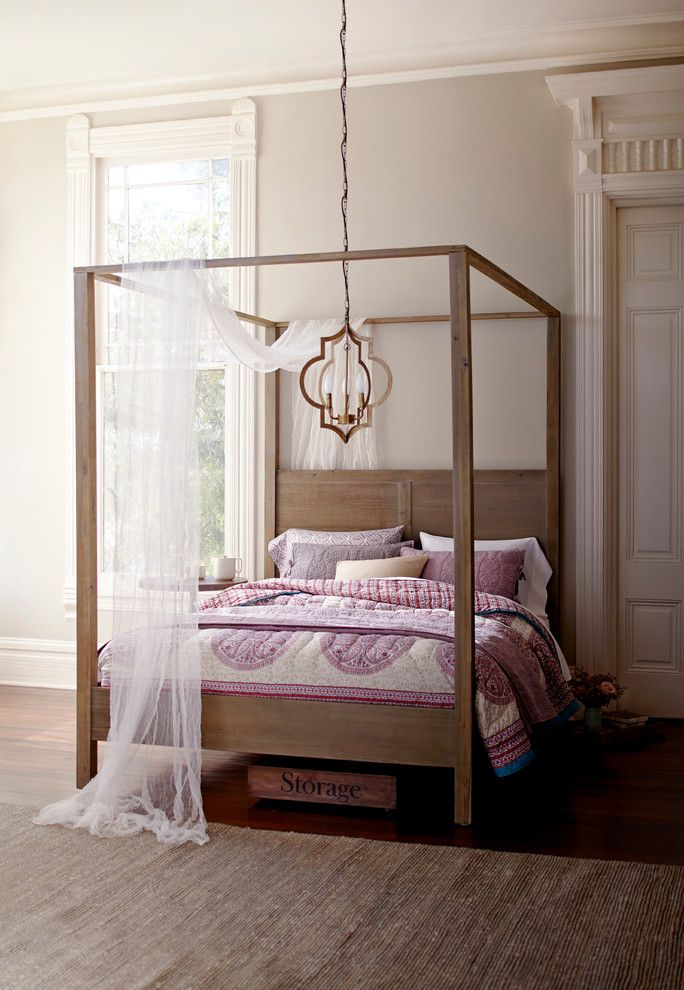 traditional wooden bed with opened canopy light purple bed