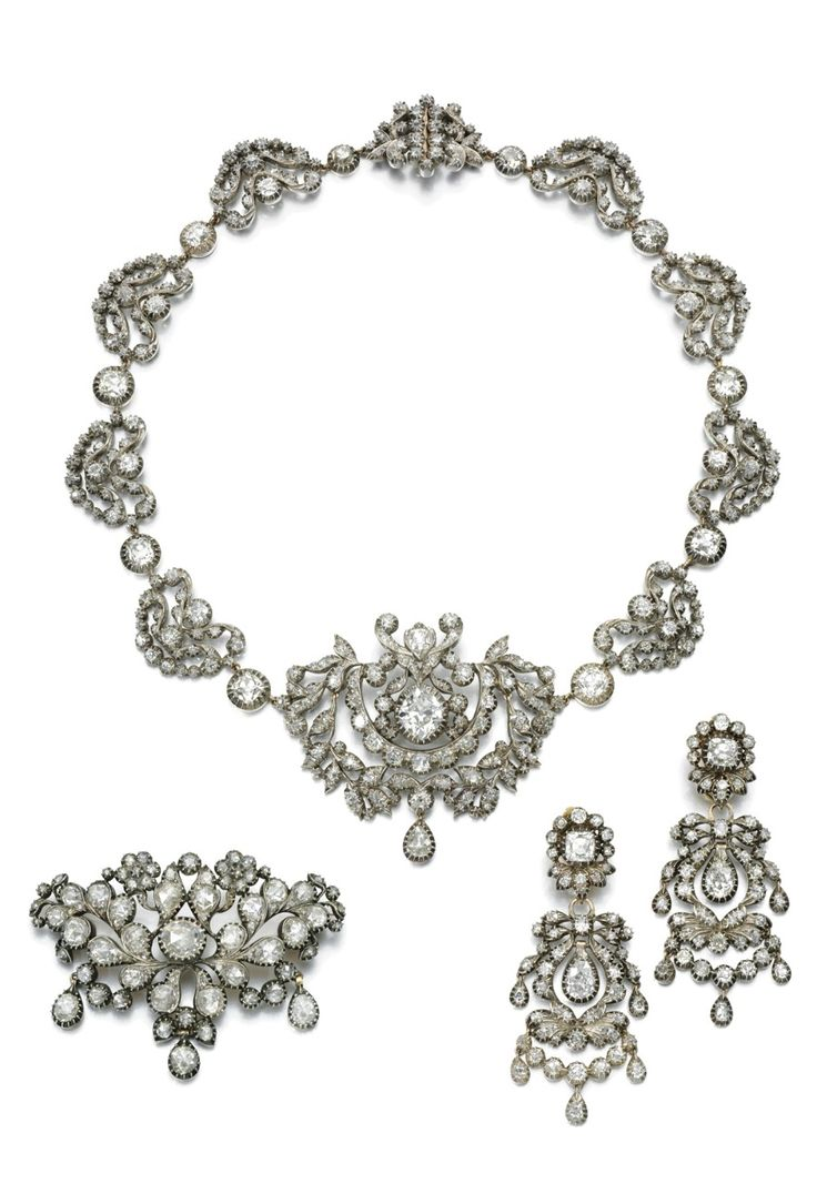 IMPRESSIVE DIAMOND DEMI-PARURE, SPANISH, EARLY 19TH CENTURY,  Comprising: a necklace composed of a series of foliate and scroll design; together with a pair of ear pendants of simlilar design each swing, and a brooch/corsage ornament of open work floral and foliate design. According to family tradition these jewels belonged to Queen Isabel II of Spain. She  presented them to her sister-in-law, the Infanta of Spain, Doña Luisa Teresa de Borbón y Borbón.