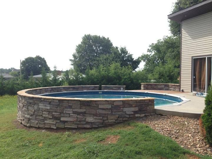 Stone wall around above ground pool. Would prefer stained cedar and stone combo instead of concrete patio.