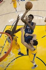 Minnesota Timberwolves guard Andrew Wiggins (22) shoots the basketball against Golden State Warriors forward Draymond Green (23) and center Andrew Bogut (12) during the second half at Oracle Arena. The Timberwolves defeated the Warriors 124-117.  #9233400