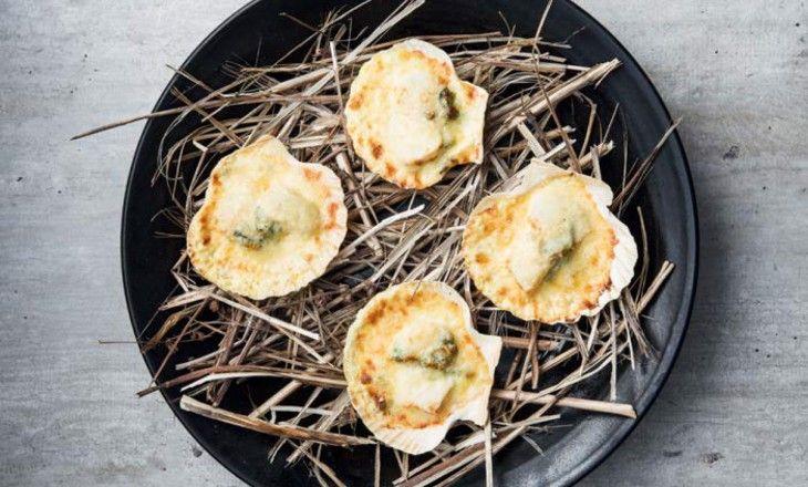 Gratinerad torsk och pilgrimsmussla täckt med vitvinssås och lagrad ost är en snabb, enkel och festlig förrätt. Torsken och pilgrimsmusslan har ungefär s
