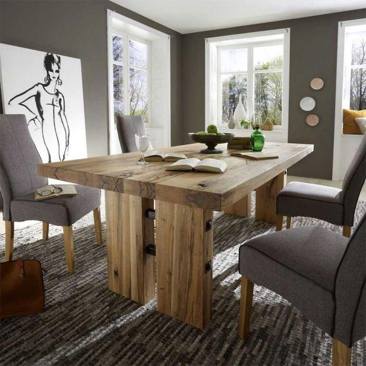 une table élégante en bois massif et des chaises grises dans la salle à manger