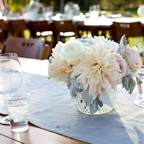 Pale champagne dahlias mixed with blush and white roses and dusty miller filled glass vases at reception tables.