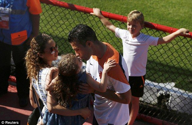 Family affair: Van Persie gives Dina, being held by his wife Bouchra Elbali, a kiss after ...