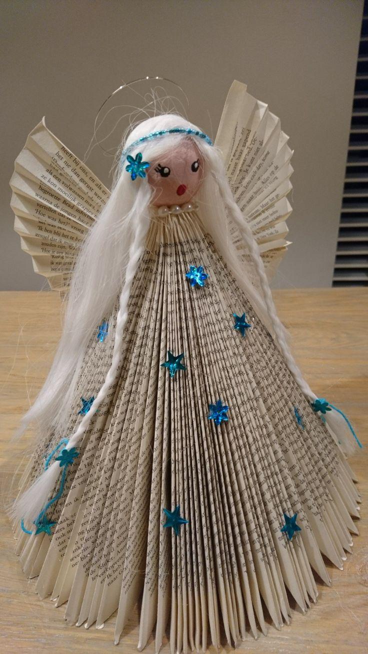 Boek de blaadjes gevouwen. Hoofd geschilderd, boven op de top geplakt met een lijmpistool. Haar van een oude carnaval pruik gebruikt. En alles versierd. Klaar is het elfje