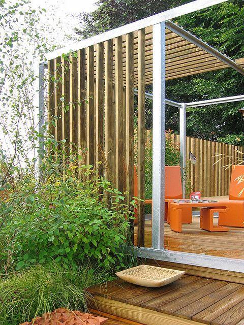 minimalist gazebo of wood and metal with orange furniture