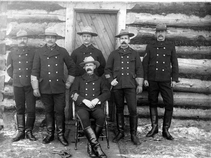 North-West Mounted Police posed in front of log cabin, Dawson, Yukon Territory, ca. 1898. (Canada)