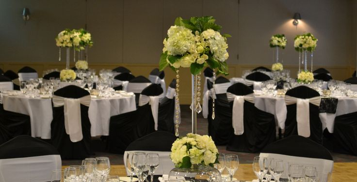 Black and white wedding reception. Tall elegant white floral arrangements with hanging crystal garlands. Styled by Greenstone Events.
