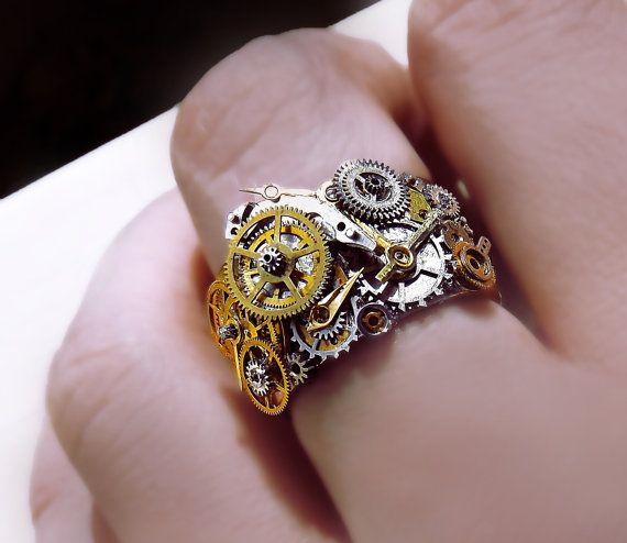 ilusión mecánico  Anillo unisex Steampunk, que consiste en una banda de acero inoxidable plata adornado con partes de relojes antiguos, cuidadosamente arreglado y rubíes.  Este anillo es muy amplia, mide poco menos de 2cm de ancho y contiene un detalle mucho más que mis otros anillos steampunk.  Altamente detallado, único y sorprendente. El reloj de piezas se han pulido para que capturan la luz maravillosamente.  Este anillo es de muy alta calidad y no manchar debido a la venda de acero…
