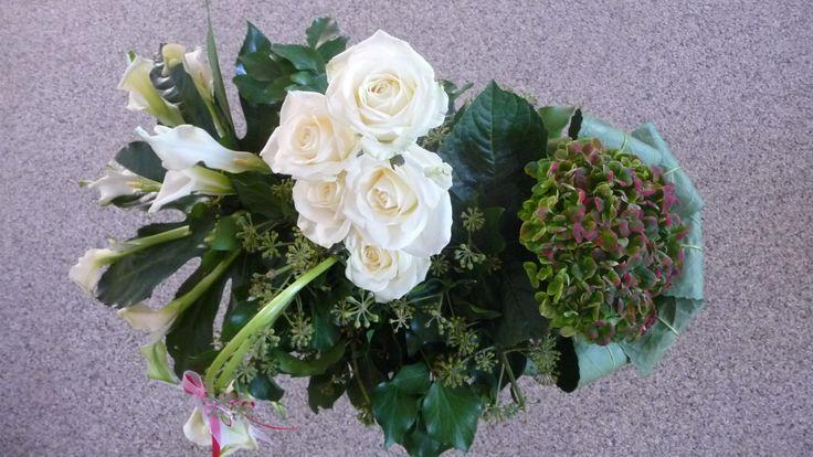 Het bloemstuk van bovenaf gezien. Bloemstuk voor in de kerk gemaakt. calla's, hortensia, rozen, klimop en vingerblad.