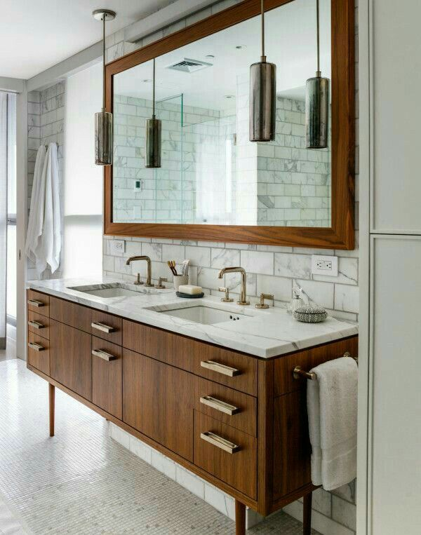 and mirror frame offer a warming contrast to the sleekness of the marble wall tiles and marble vanity countertop in this elegant modern bathroom